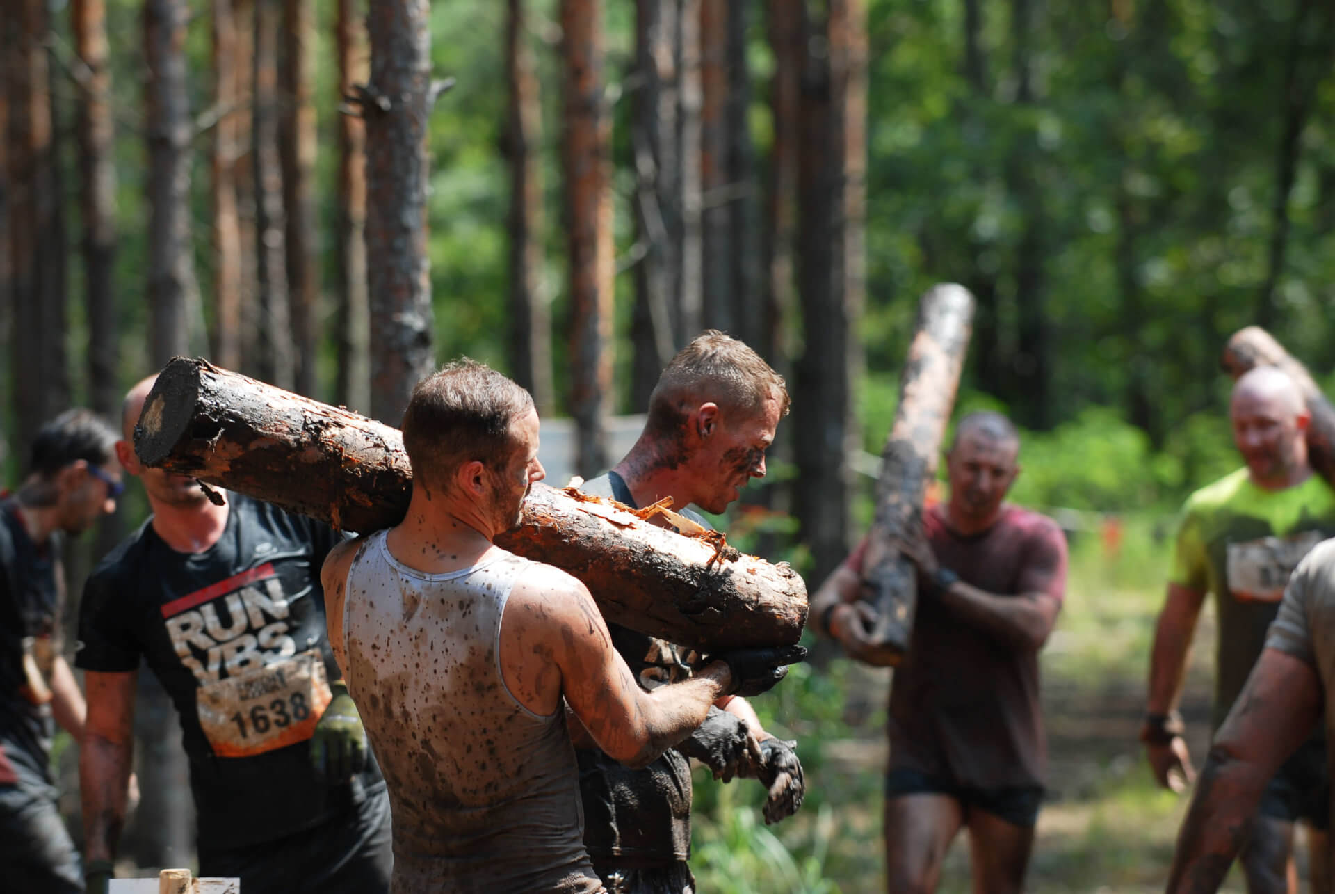 Teilnehmer heben einen Baumstamm